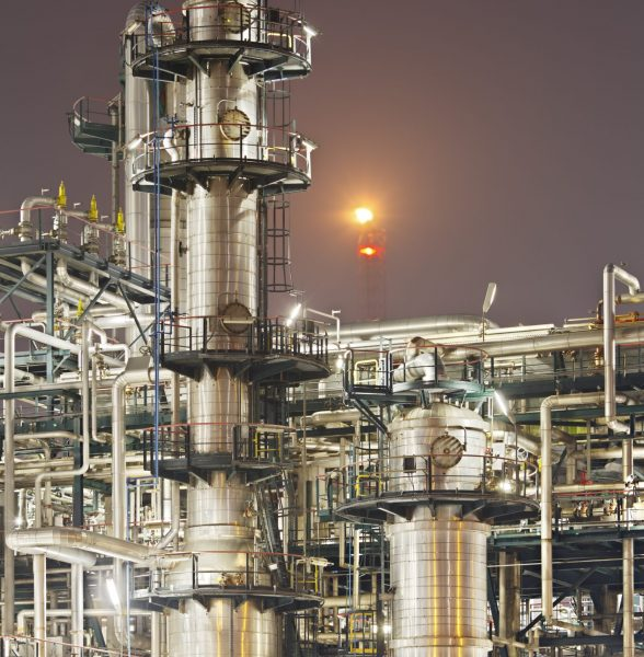 An oil refinery detail shot with a flare in the background.